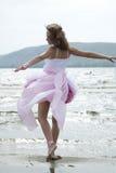 Die schöne junge Frau tanzt auf einen Strand Stockfotografie