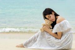 Die schöne junge Frau, die traurig sind und die deprimierte Frau, die mit Teddybären tief ist, sind Stockfoto