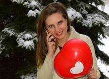 Die schöne junge glückliche Frau, welche die Blondine durch den Handy spricht Stockbilder