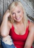 Die schöne junge lächelnde Frau, lehnt sich am Zaun Stockfotos