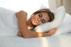 Die schöne junge schlafende Frau, beim im Bett bequem liegen und himmlisch Sonnenstrahl dämmern auf ihrem Gesicht lizenzfreie stockfotos