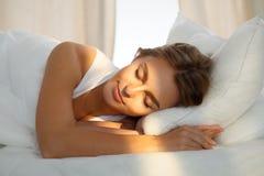 Die schöne junge schlafende Frau, beim im Bett bequem liegen und himmlisch Sonnenstrahl dämmern auf ihrem Gesicht stockfoto