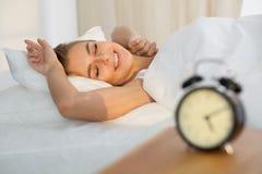 Die schöne junge schlafende Frau, beim im Bett bequem liegen und himmlisch Sonnenstrahl dämmern auf ihrem Gesicht lizenzfreies stockfoto