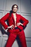 Die schöne junge sexy Brunettefrau, die stilvolles Design der roten Jacke und modernes Kostüm mit Juwel, beige Fersen trägt, besc Lizenzfreies Stockfoto