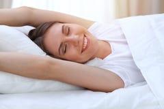 Die schöne junge und glückliche Frau, die Hände ausdehnt, beim im Bett bequem liegen und vor himmlisch lächeln wachen herein auf lizenzfreie stockbilder