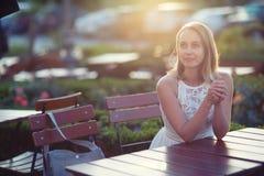 Die schöne kaukasische Frau, die draußen am Tisch, Sonnenunterganglebensstil sitzt, schoss mit Kopienraum lizenzfreie stockfotografie