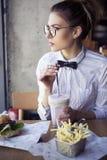 Die schöne kaukasische junge Frau, die Schnellimbiß des Mittagessens isst, briet Topf Stockfotos