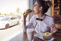 Die schöne kaukasische junge Frau, die Schnellimbiß des Mittagessens isst, briet Topf Lizenzfreies Stockfoto