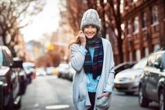 Die schöne lächelnde Frau, die auf die Stadtstraße trägt zufällige Art geht, kleidet Stockfotografie