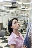 Die schöne mittlere erwachsene Frau, die Plastik setzt, um zu trocknen, säuberte beim oben schauen Stockfotos