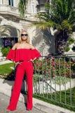 Die schöne phänomenale erstaunliche elegante sexy blonde vorbildliche Luxusfrau, die ein rotes Kleid trägt, läuft die Straßen für Stockfotos