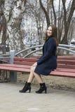 Die schöne russische Frau sitzt auf einer Bank im Park Lizenzfreie Stockfotografie