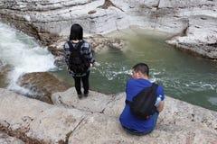Die schöne Schlucht mit Türkisteich und Wasserfall in den Bergen, wie der Tourist entlang die Spur ging Junges Mädchen des Reisen Lizenzfreies Stockfoto