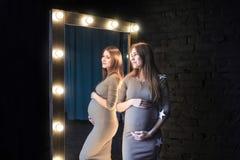 Die schöne schwangere Frau in der Spiegelreflexion Stockbild