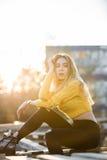 Die schöne sexy blonde junge Frau, die wie Jennifer Aniston aussieht, sitzt in den hölzernen Paletten der Ruinen Lizenzfreie Stockfotos