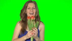 Die schöne sinnliche kaukasische Frau, die rote Tulpe hält und riecht, blüht stock footage