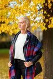 Die schöne stilvolle blonde Frau, die unter Gelb steht, lässt Herbstbaum Stockfotos