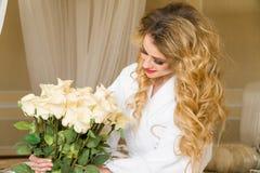 Die schöne verlockende Frau, die mit der Kamera flirtet, sitzt auf dem Bett mit einem großen Blumenstrauß von weißen Rosen im Wei Lizenzfreies Stockbild
