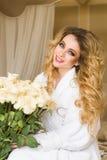 Die schöne verlockende Frau, die mit der Kamera flirtet, sitzt auf dem Bett mit einem großen Blumenstrauß von weißen Rosen im Wei Stockfotografie