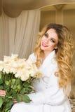 Die schöne verlockende Frau, die mit der Kamera flirtet, sitzt auf dem Bett mit einem großen Blumenstrauß von weißen Rosen im Wei Lizenzfreie Stockbilder