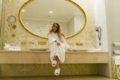 Die schöne verlockende Frau, die mit der Kamera flirtet, sitzt in ihrem Badezimmer Junge Frau der Schönheit Stockbilder