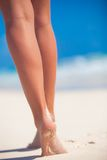 Die schönen glatten Beine der Frauen auf weißem Sand setzen auf den Strand Stockfotos
