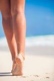 Die schönen glatten Beine der Frauen auf weißem Sand setzen auf den Strand Lizenzfreie Stockfotografie