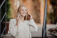 Die schönen jungen Blondine, die auf die Straße gehen und an einem Handy, das Mädchen sprechen, lachen und lächeln Stockbilder
