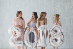 Die schönen jungen Frauen, die Silber 2018 halten, unterzeichnen Ballone und das Lächeln an der Kamera Partei des neuen Jahres Lizenzfreies Stockfoto