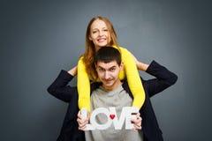 Die schönen lächelnden Paare, die Wort halten, LIEBEN und zusammen stehen auf grauem Hintergrund Stockbild