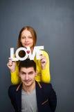 Die schönen lächelnden Paare, die Wort halten, LIEBEN, zusammen auf grauem Hintergrund Stockfotos