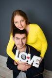 Die schönen lächelnden Paare, die Wort halten, LIEBEN, zusammen auf grauem Hintergrund Stockfotografie