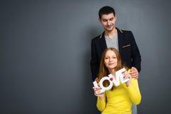 Die schönen lächelnden Paare, die Wort halten, LIEBEN, zusammen auf grauem Hintergrund Lizenzfreie Stockfotos