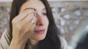Die Schönheit, die einen Spiegel hält und Augenbrauen auf Gesicht zeichnet - bilden Sie Konzepte stock video