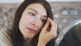 Die Schönheit, die einen Spiegel hält und Augenbrauen auf Gesicht zeichnet - bilden Sie Konzepte stock footage