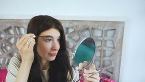 Die Schönheit, die einen Spiegel hält und Augenbrauen auf Gesicht zeichnet - bilden Sie Konzepte stock video footage