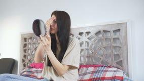Die Schönheit, die einen Spiegel hält und Creme auf Gesicht setzt - bilden Sie Konzepte stock video footage