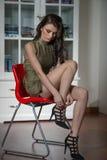 Die Schönheit, die ihre Beine an setzen oder entfernen hohe Absätze zeigt, schwärzen Schuhe Sinnliches attraktives tragendes Klei Lizenzfreies Stockbild