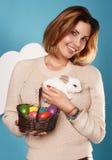 Die Schönheit, die weißen kleinen Osterhasen hält, aalte sich Eier Stockbild