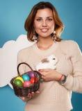 Die Schönheit, die weißen kleinen Osterhasen hält, aalte sich Eier Stockbilder