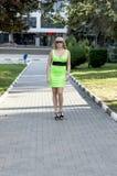 Die Schönheit in einem grünen Kleid geht auf den Bürgersteig Lizenzfreies Stockbild
