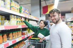 Die Schönheit eines jungen Paares kauft eingemachtes Gemüse in einem Supermarkt Porträt eines lächelnden Mannes in einem Supermar stockfotos