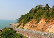 Die Schönheitskurvenstraße zum Meer und der Strand mit blauem Himmel Stockbild