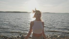 Die sch?ne athletische Frau, die Morgen?bungen auf der K?ste tut Strand und Sonnenaufgang auf dem Hintergrund stock video