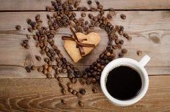 Die Schale von coffe und von Rahmen-Herzen von den Kaffeebohnen und von zwei Plätzchen Stockfoto
