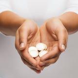 Die schalenförmigen Hände der Frau, die Euromünzen zeigen Lizenzfreie Stockfotografie
