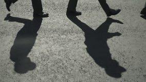 Die Schatten von gehenden Soldaten auf dem Asphalt stock video