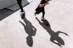 Die Schatten von zwei Männern, die draußen auf den Skateboards auf dem Boden in einem Rochenpark am sonnigen Tag stehen stockfotografie