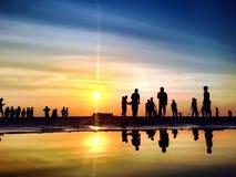 Die Schattenbild-Leute auf dem Strand bei Sonnenuntergang Stockfotos