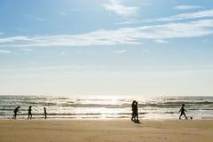 Die Schattenbilder einer Gruppe von Personen, die am Strand geht lizenzfreie stockbilder